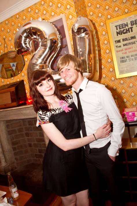 Couple posing together in front of 21st birthday balloons