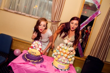 Two women blowing out birthday cake candles