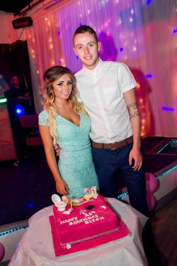 woman and man posing together in front of a 21st birthday cake