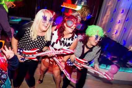 three women wearing oversized glasses and dancing in unison with balloon guitars