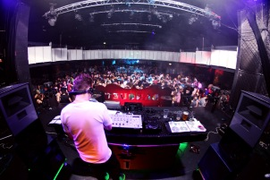 Shot from behind the DJ deck over looking the crowd at a nightclub