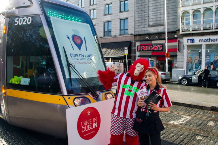 TGI Fridays Dine in Dublin staff members pose next to the luas with the Dublin restaurant in the background