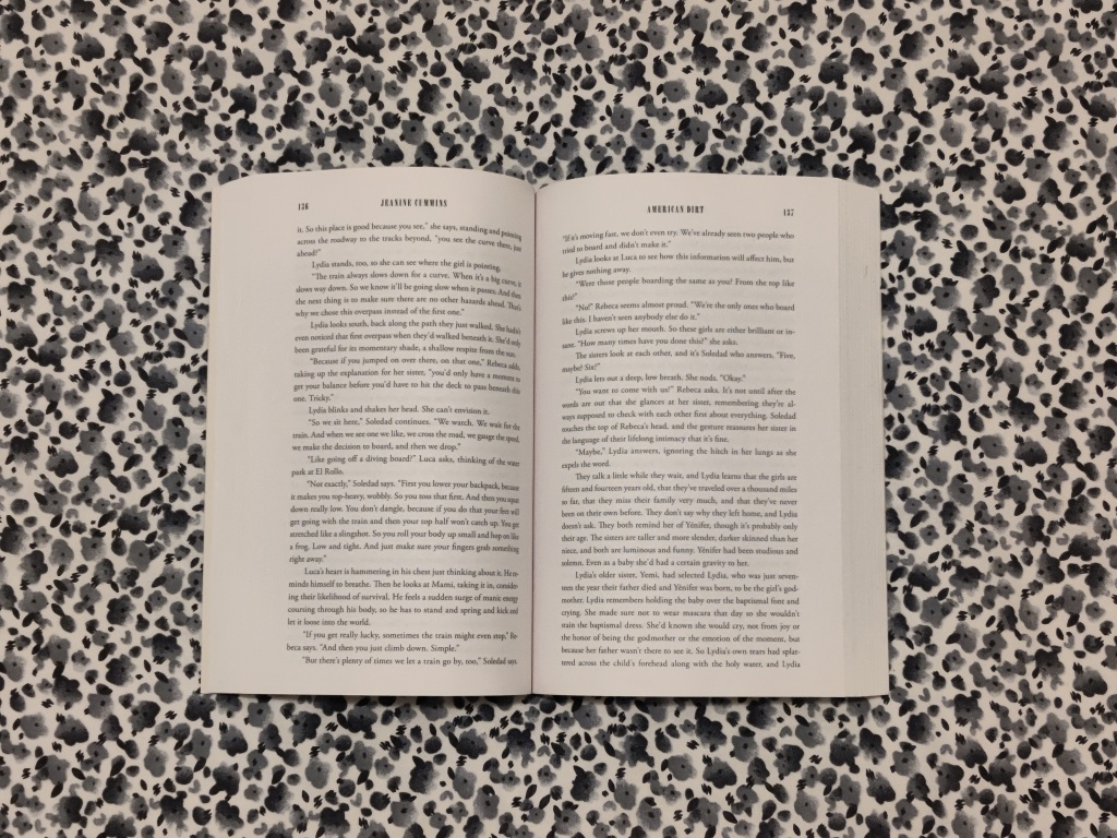 A book called American Dirt, laid open on a floral bedsheet
